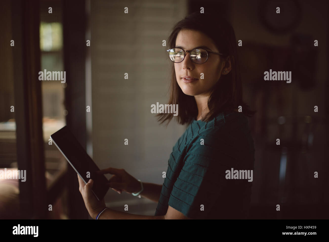 Portrait of woman using digital table at home - Stock Image