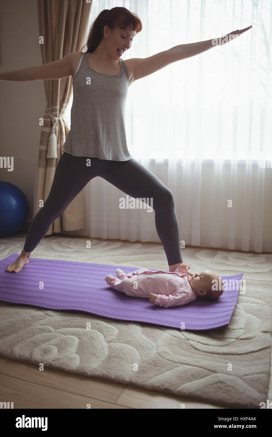Happy mother doing warrior pose while looking at baby in house - Stock Image