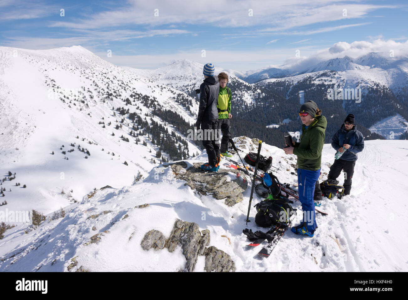 Group of ski mountaineers having a break on top of a snowy mountain, Triebenfeldkogel, Styrian Alps, Austria. Stock Photo