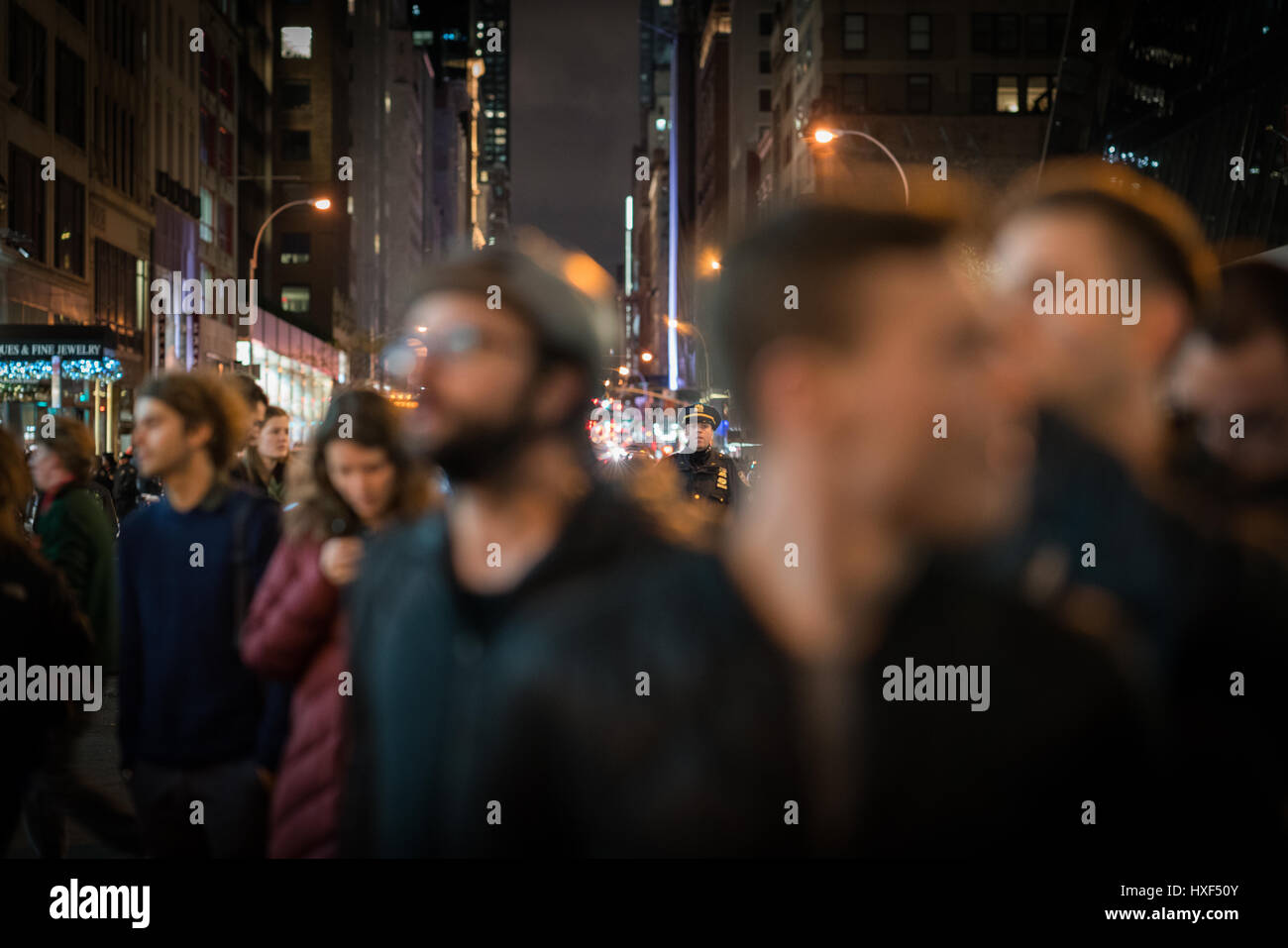 NYPD officer watches the crowd as they slowly disperse at the end anti-Trump rally. - Stock Image