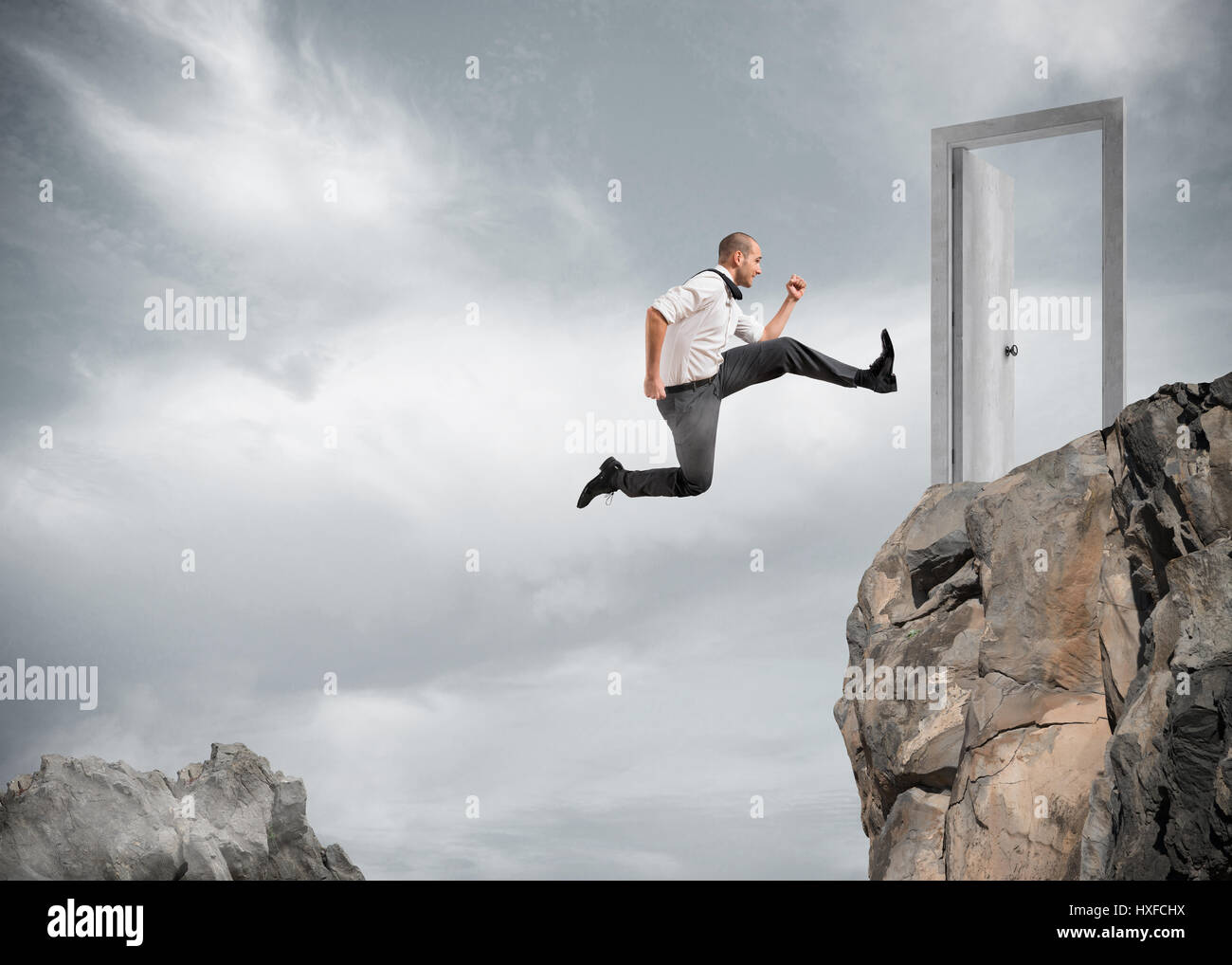 Businessman jumping over the mountains to reach a door - Stock Image