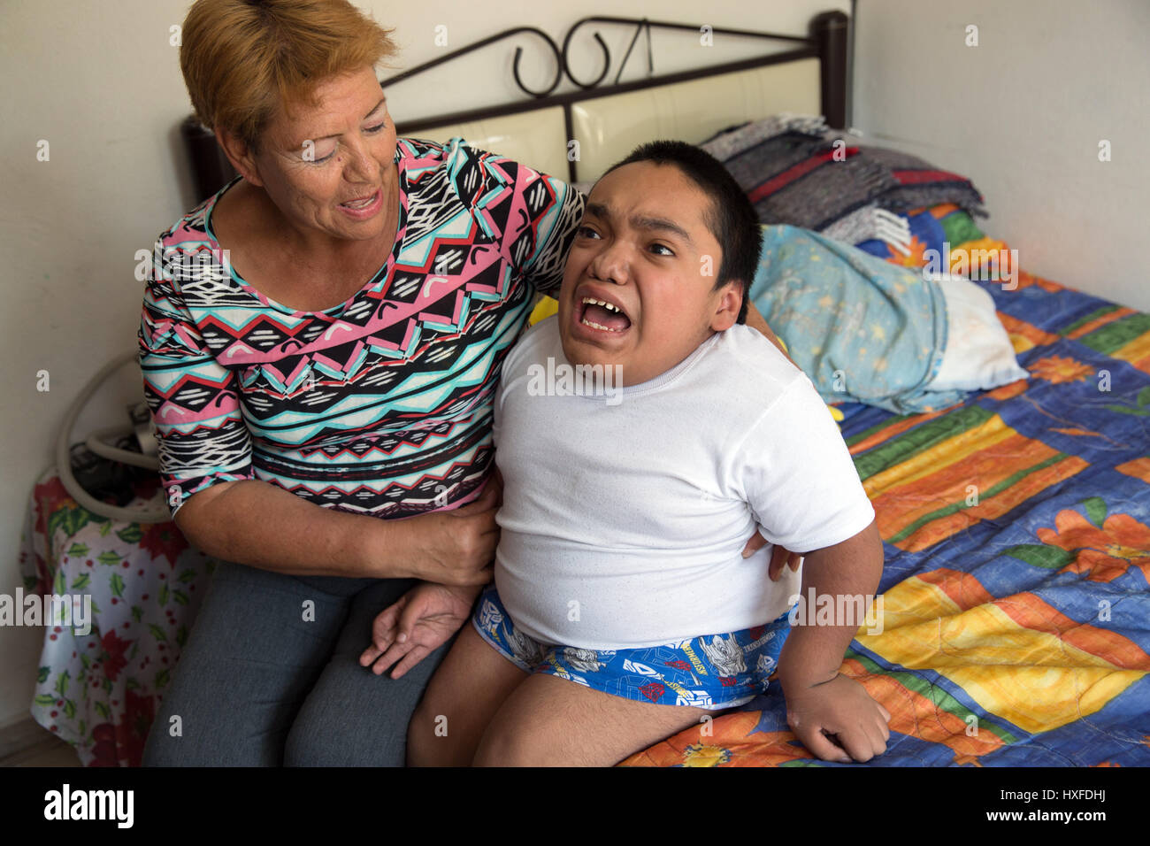 Joaquin Eduardo Torres Gil, 14, is pictured wth his mother Joaquina in his bedroom in Mexico City, Mexico, on February - Stock Image