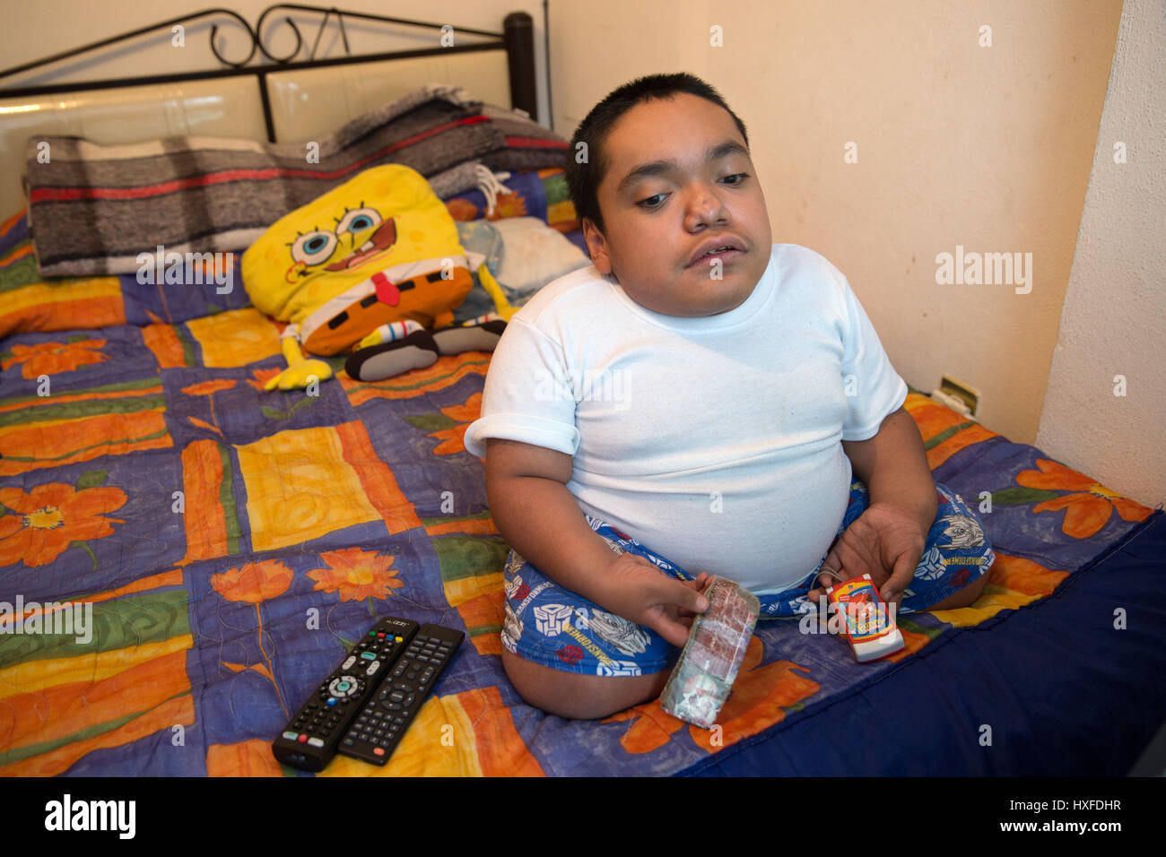 Joaquin Eduardo Torres Gil, 14, watching television in his bedroom in Mexico City, Mexico, on February 16, 2017. - Stock Image