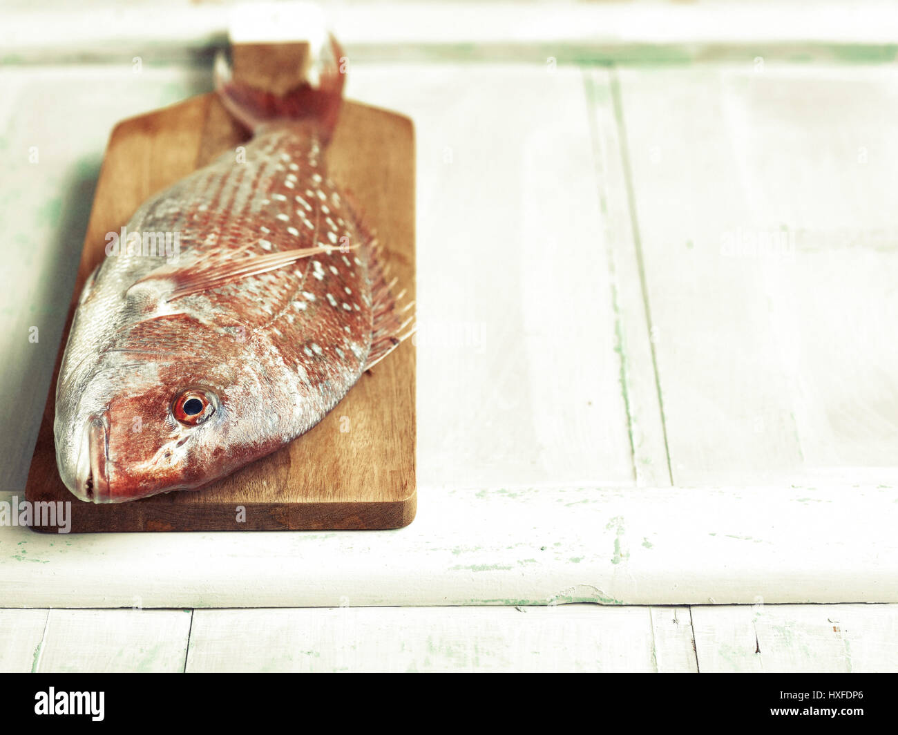 Fresh red snapper fish on chopping board ready for filleting Stock Photo