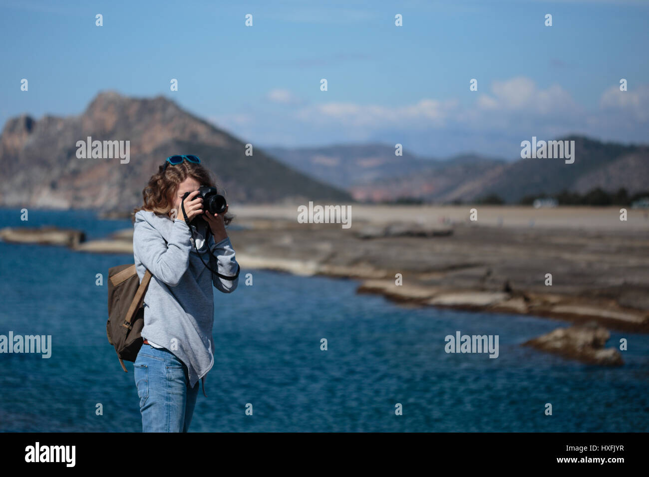 Young woman wearing jeans gray jacket and backpack standing and photographing rock ribbed beach in Gazipasha Alanya Stock Photo