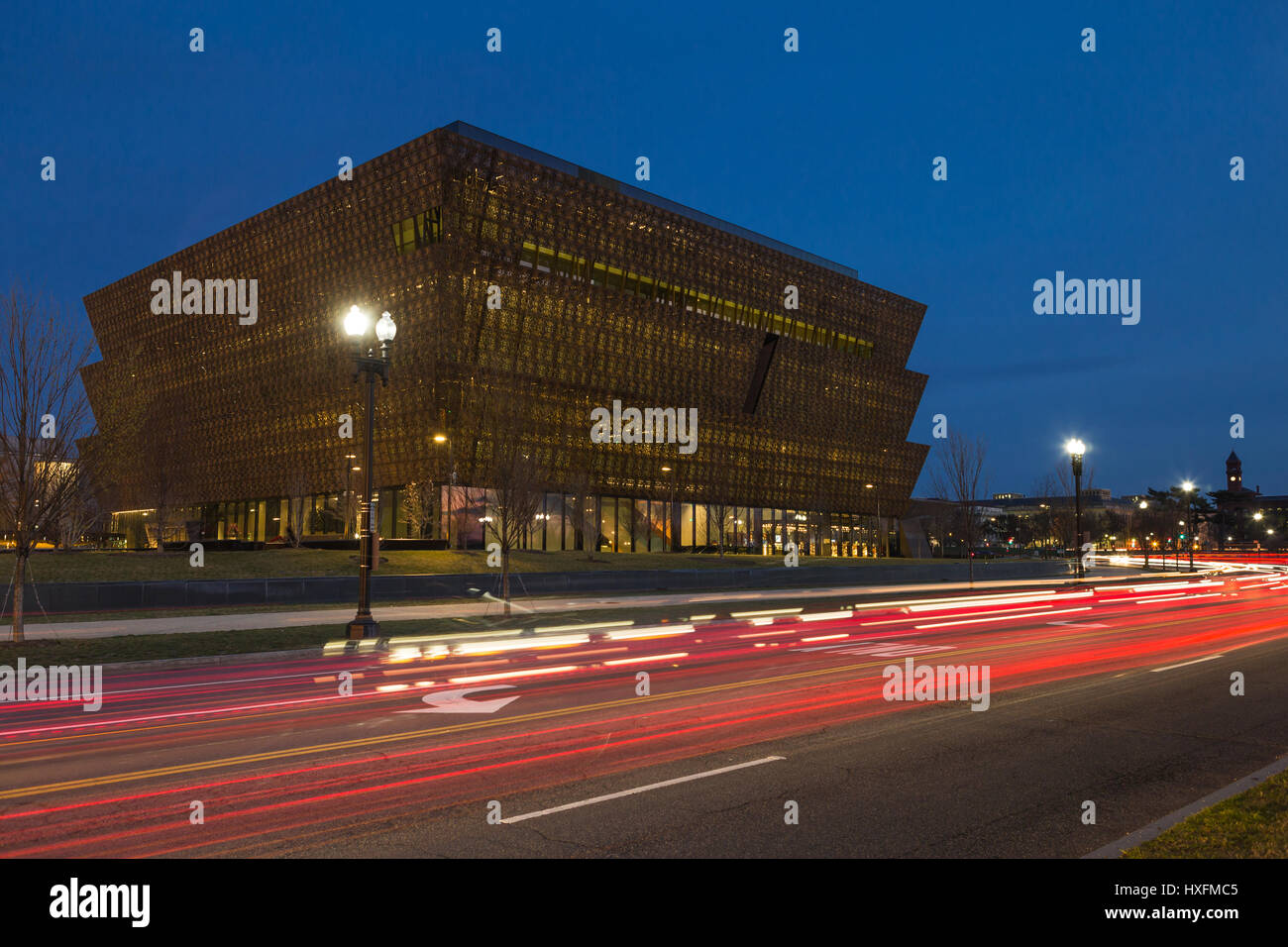 Traffic creates light trails at twilight outside the Smithsonian National Museum of African American History and - Stock Image