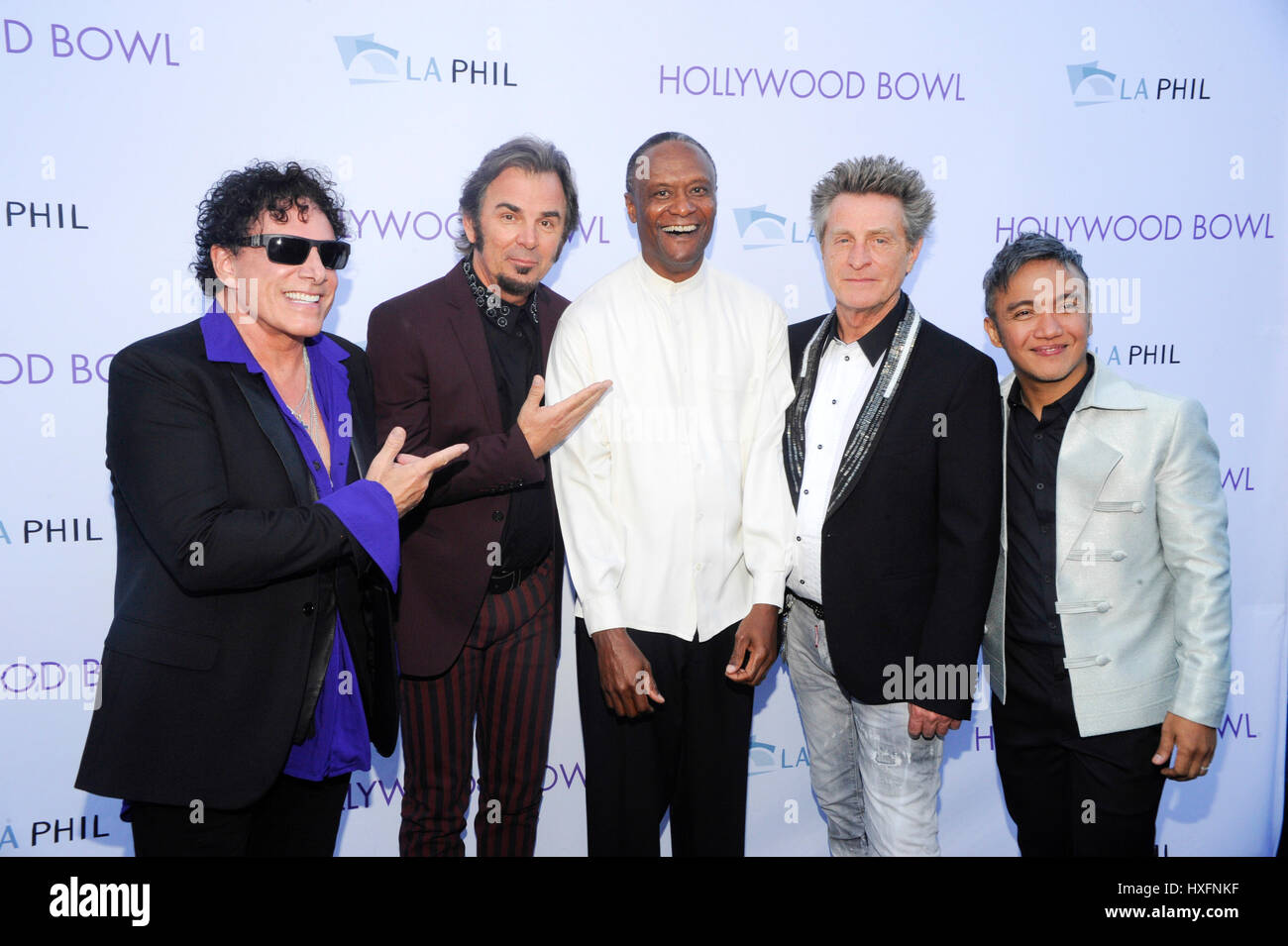 (L-R) Neal Schon, Jonathan Cain, Ross Valory and Arnel Pineda of rock band Journey with Thomas Wilkins conductor - Stock Image