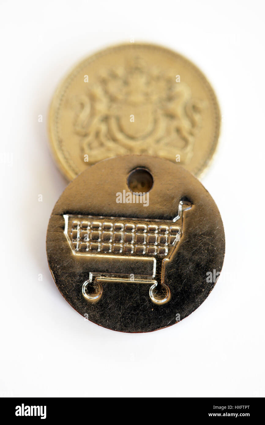 One pound coin and a same sized supermarket trolley token. A new UK  £1 coin was introduced on 28 March 2017 - Stock Image