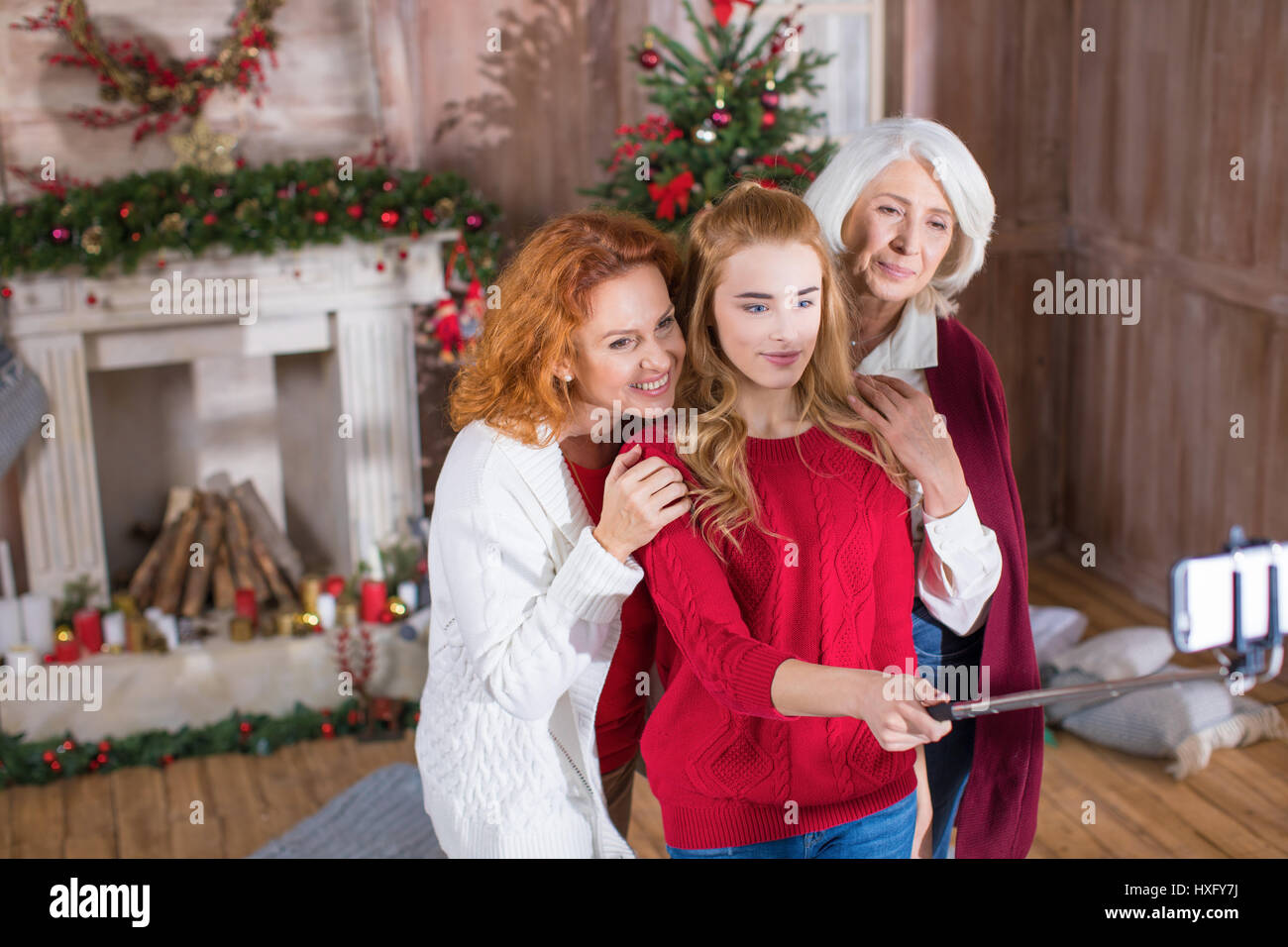 Happy family from three generations taking selfie at christmastime - Stock Image