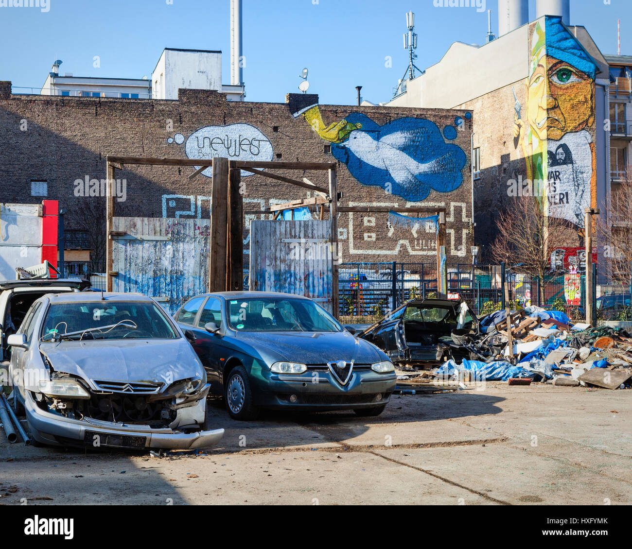 Berlin buildings with mural street art on firewalls of building, hand and dove,man holding gun.Junkyard with wrecked - Stock Image
