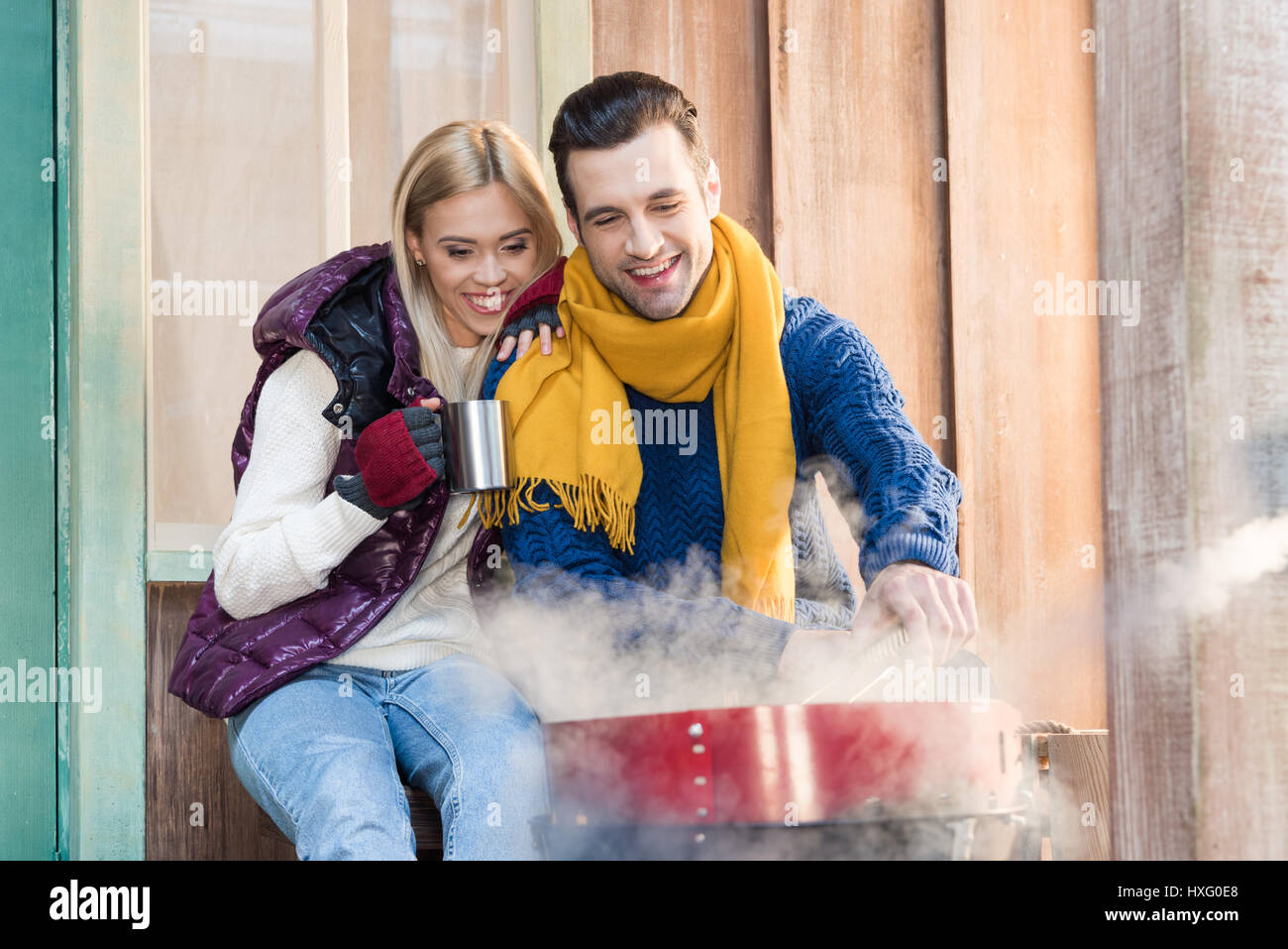Happy young couple in warm clothes sitting together near grill on porch - Stock Image