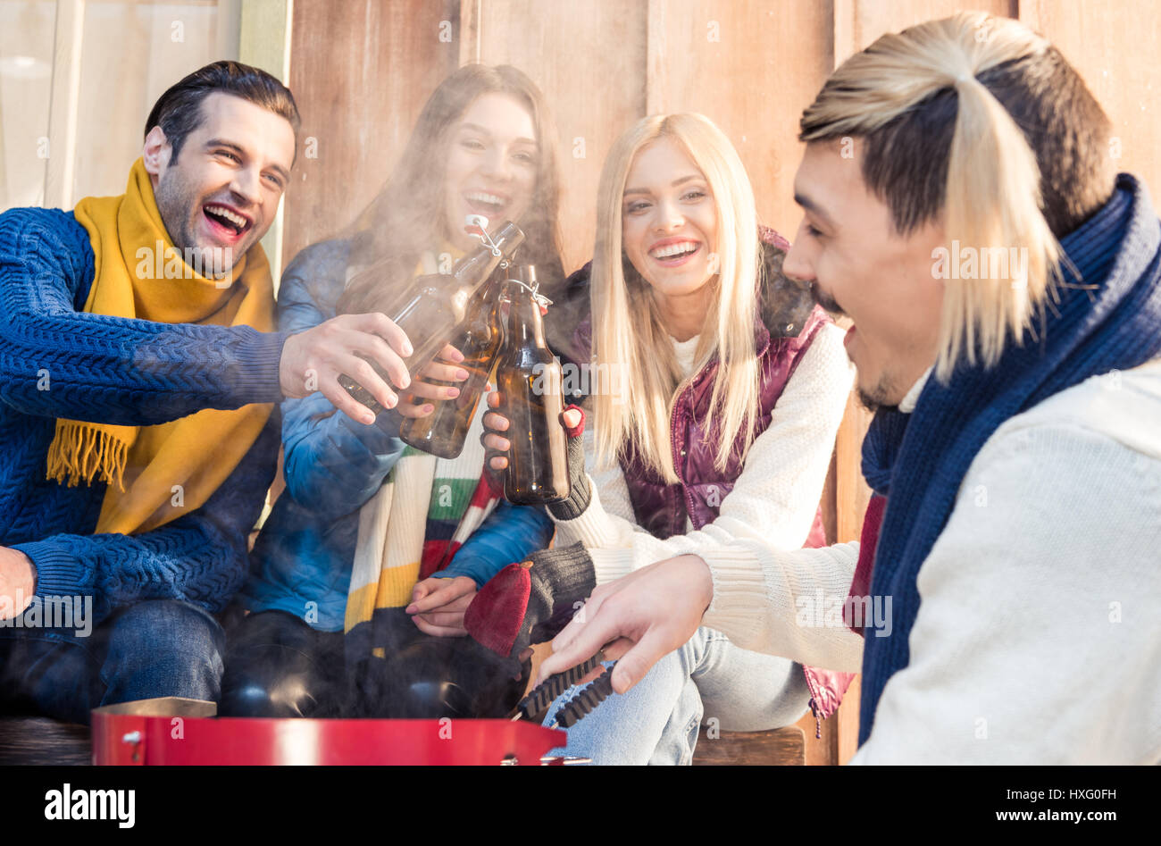 excited friends clinking bottles of beer at barbecue - Stock Image