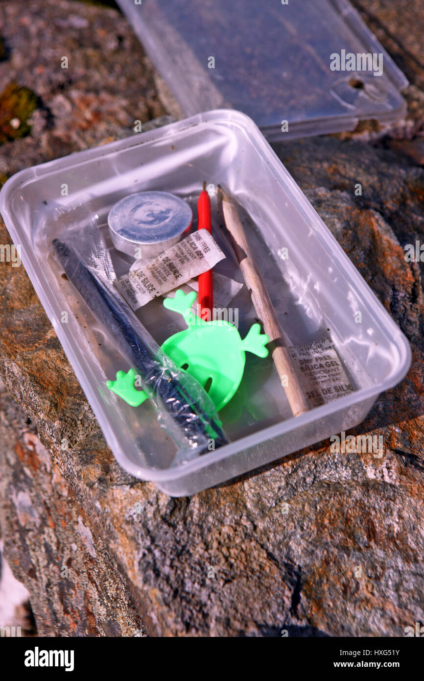 Geocaching waterproof container pen pencil and some trinkets at Tom na h-Airidh above Helensburgh, Scotland UK - Stock Image