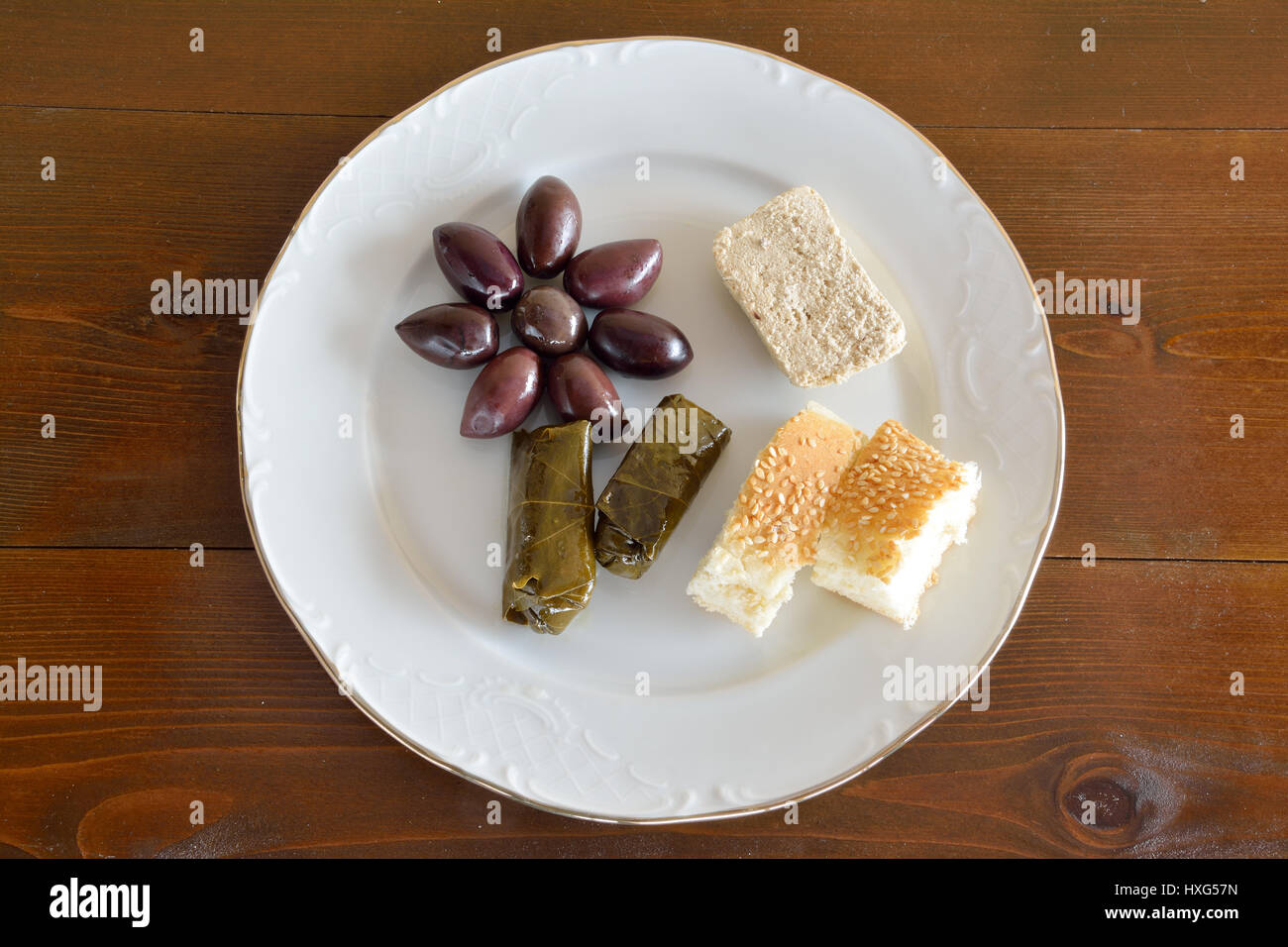 Fasting food concept of plate with olives, dolma, sunflower halva and lagana - Stock Image