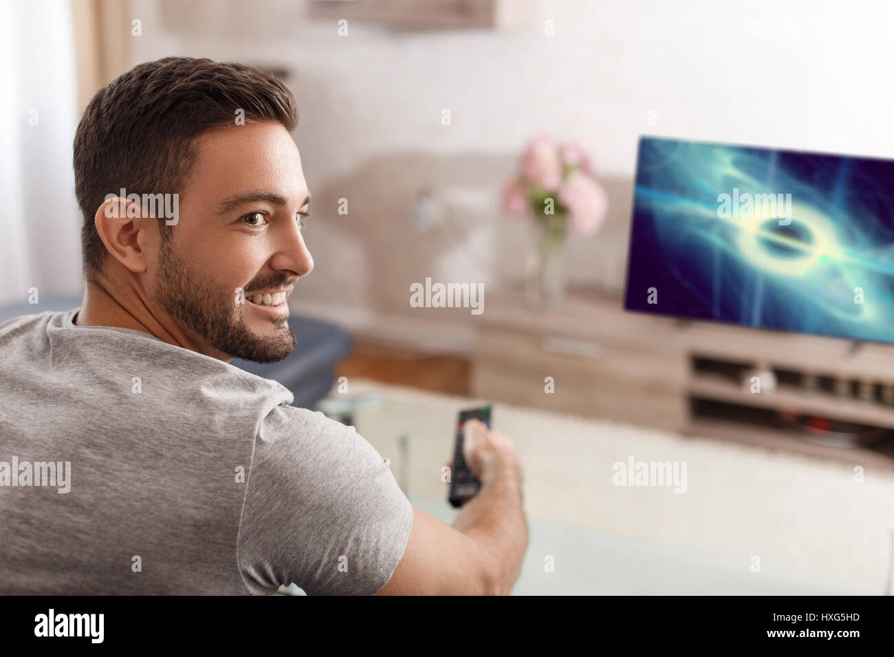 Excited man switch TV to sci-fi movie by remote control - Stock Image