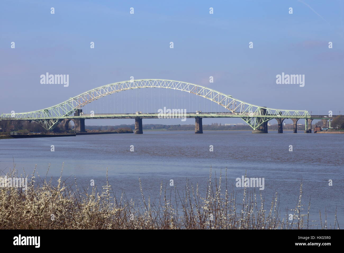 The Silver Jubilee Bridge at Runcorn crossing the Manchester Ship Canal and the River Mersey. Rail bridge of stone - Stock Image