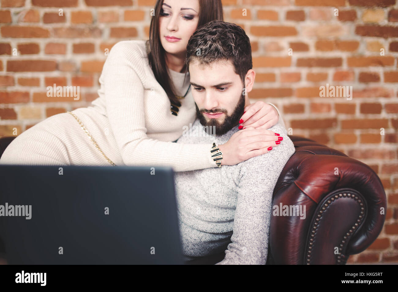 Young couple with laptop online shopping at home - Stock Image