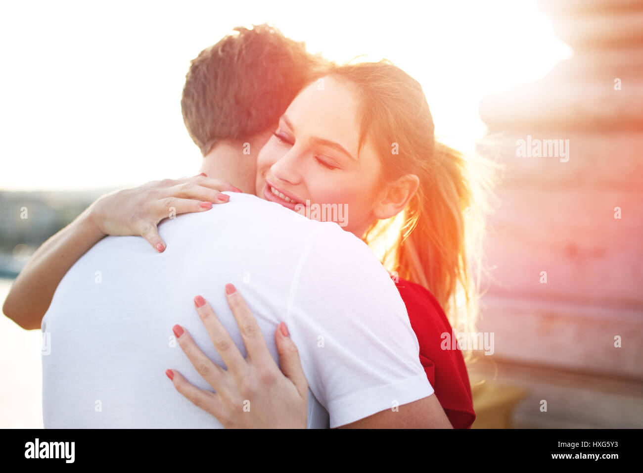 Young blonde woman embracing boyfriend outdoor - Stock Image