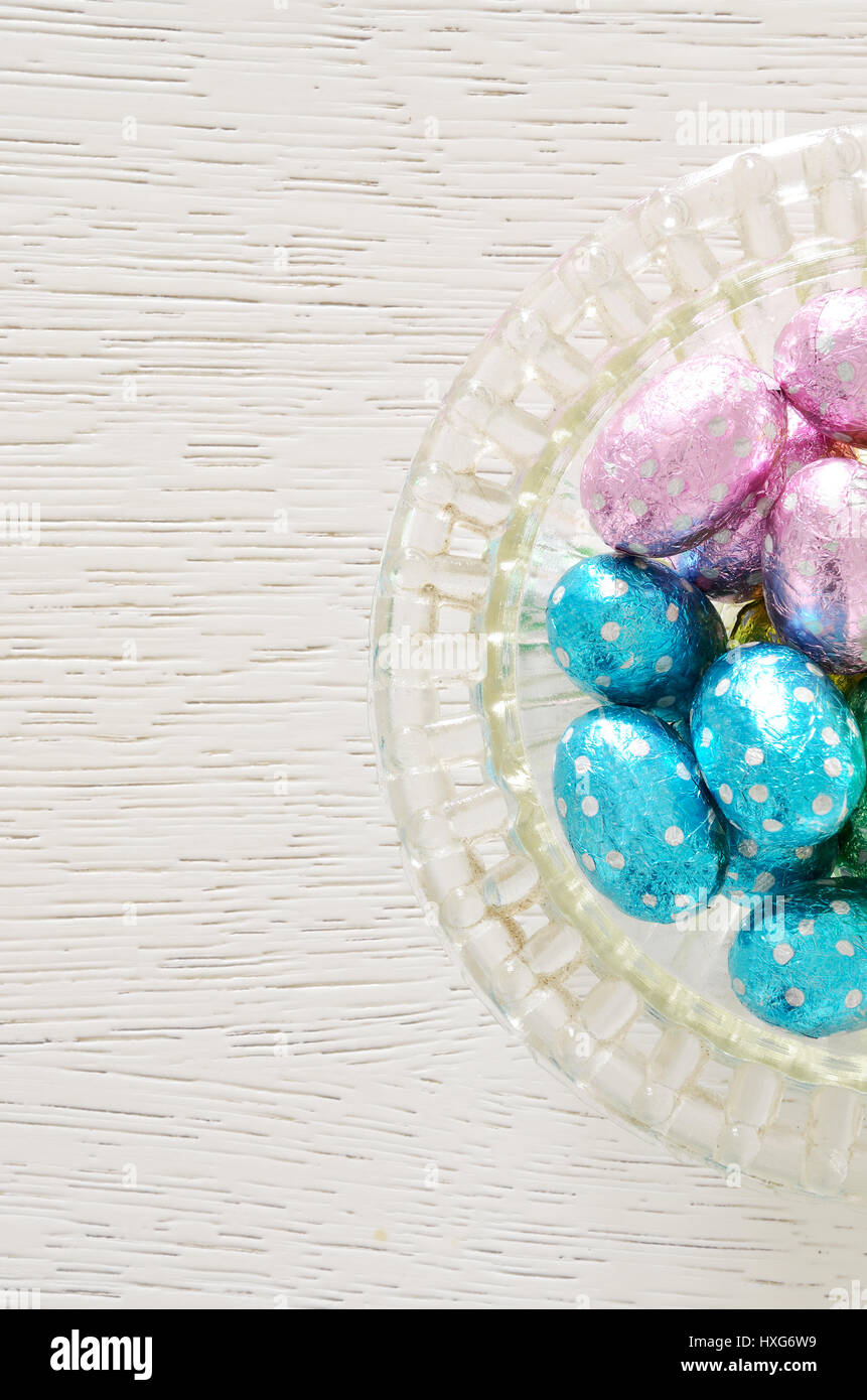 Foil Wrapped Chocolate Easter Eggs in glass bowl Stock Photo