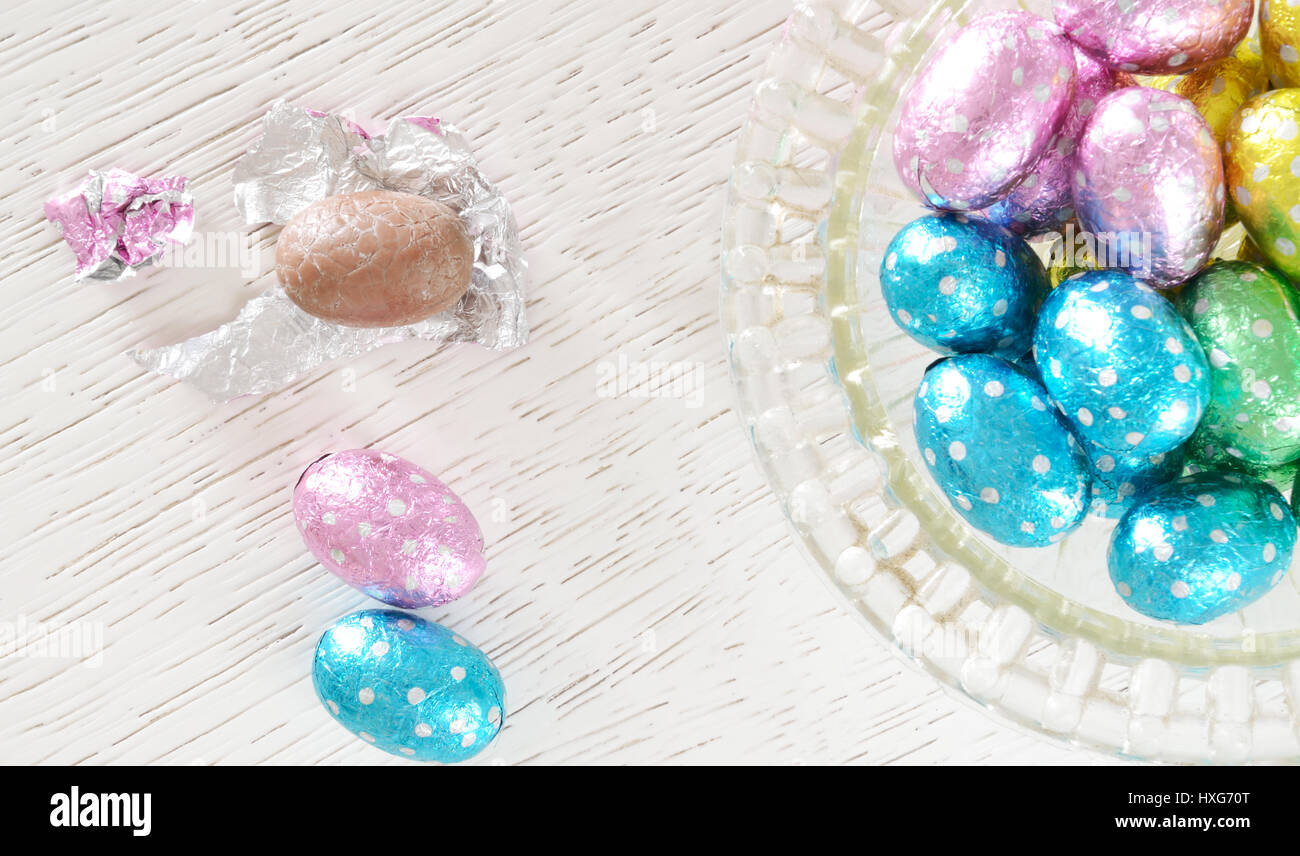 Chocolate eggs, foil wrappered, and  an unwrapped chocolate egg  beside a glass bowl full  of foil wrapped chocolate Stock Photo