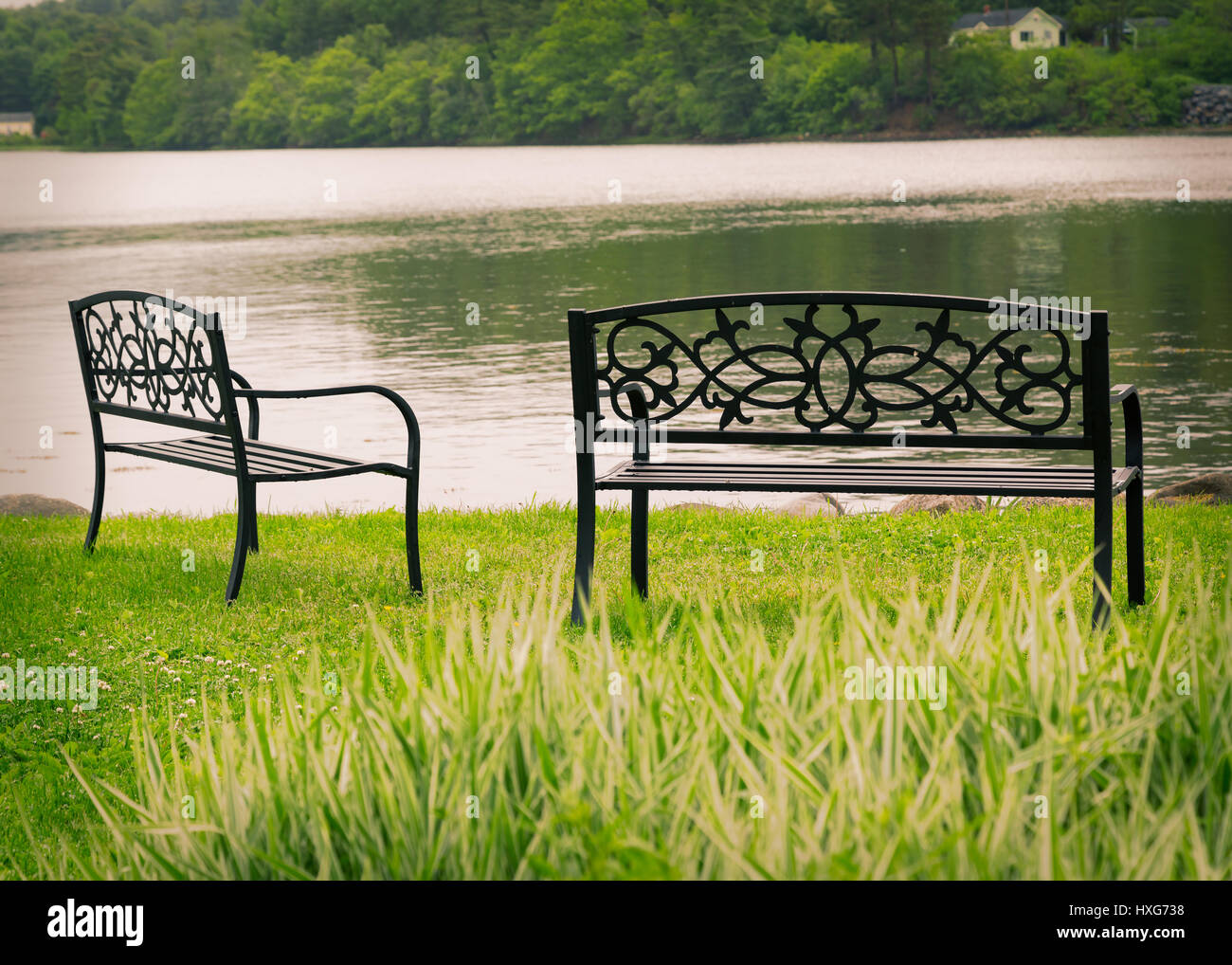 Decorative metal park benchs overlooking still water. - Stock Image