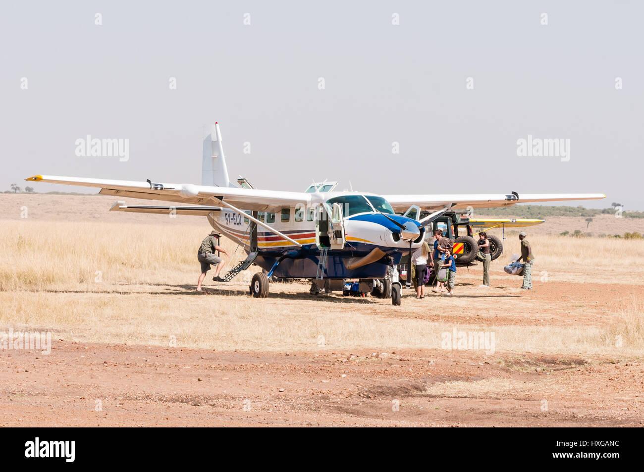 Cessna Plane Waiting On Dusty Runway While Passengers Load Aircraft, Maasai Mara - Stock Image