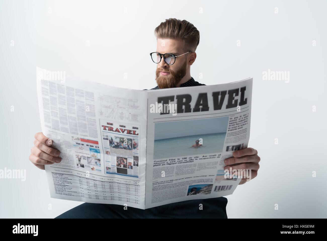 0a7188c1b9 portrait of stylish man in glasses reading newspaper on white - Stock Image