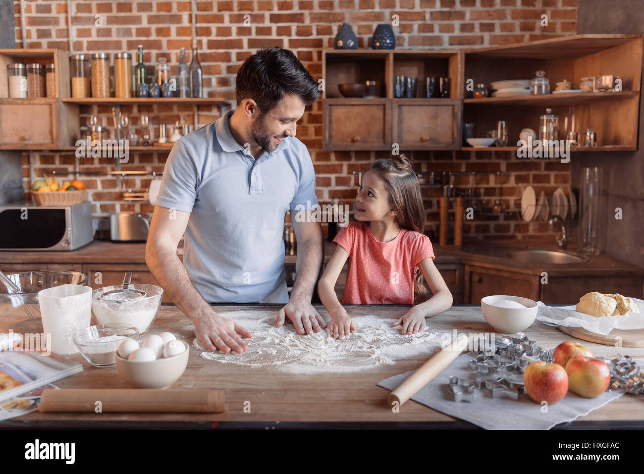 'Happy father and daughter cooking together and looking at each other in kitchen - Stock Image