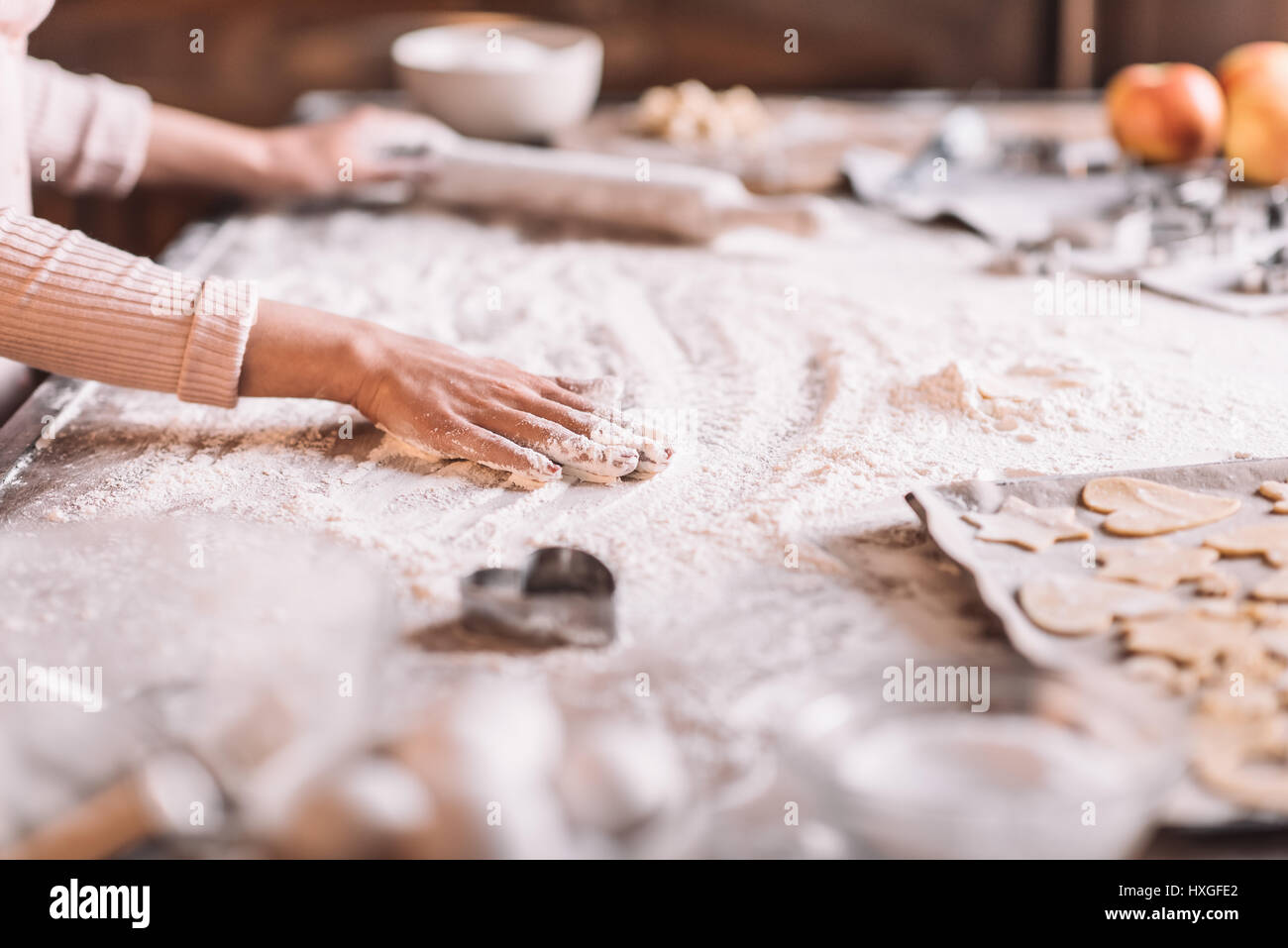 'Partial view of woman kneading dough at kitchen table - Stock Image