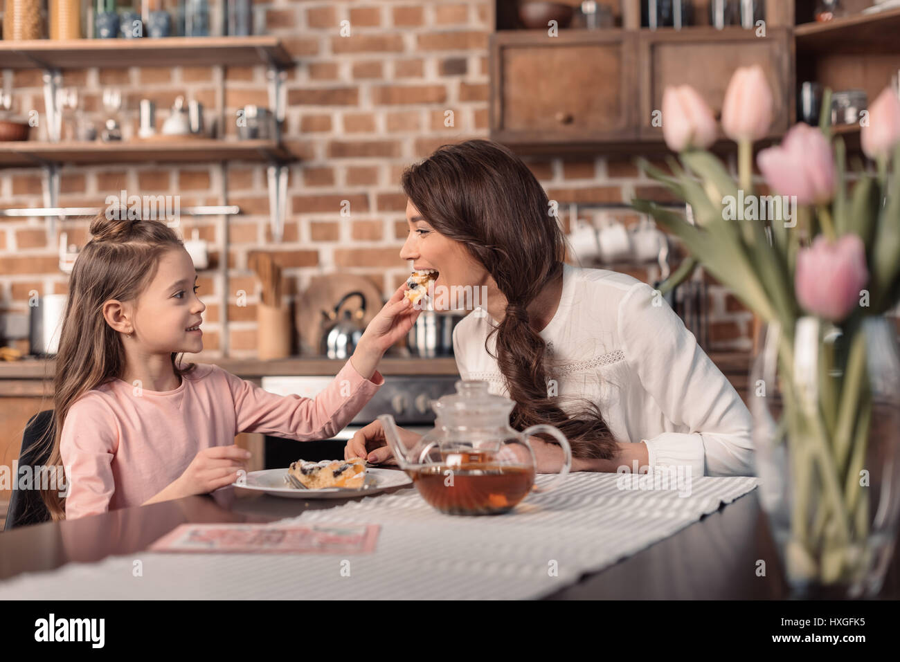 'side view of daughter feeding mother with cake on mother's day holiday in kitchen - Stock Image