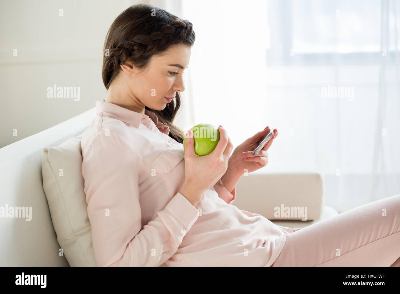 side view of concentrated woman with apple using smartphone - Stock Image