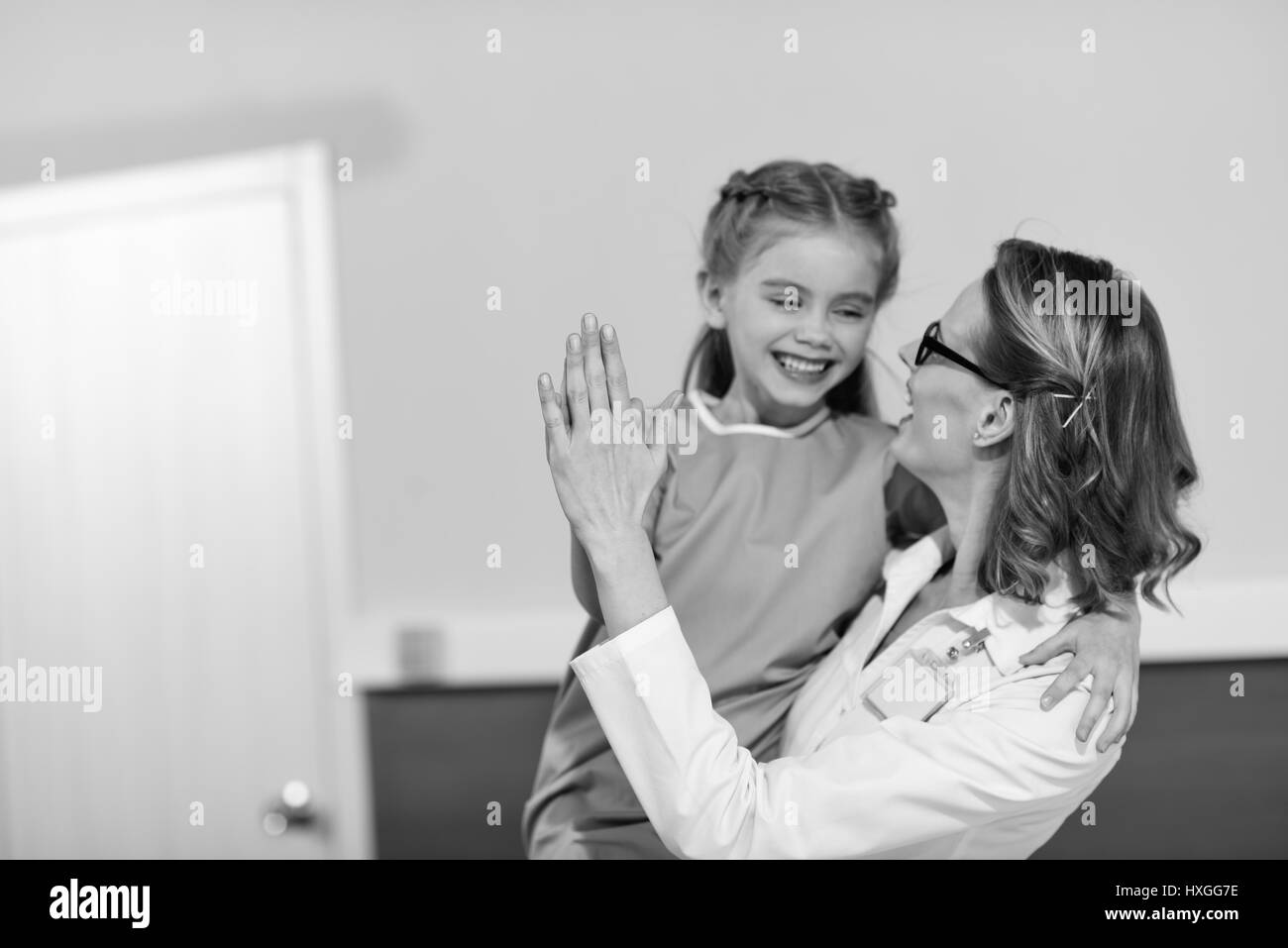 Smiling doctor and happy little girl patient looking at each other, black and white photo - Stock Image