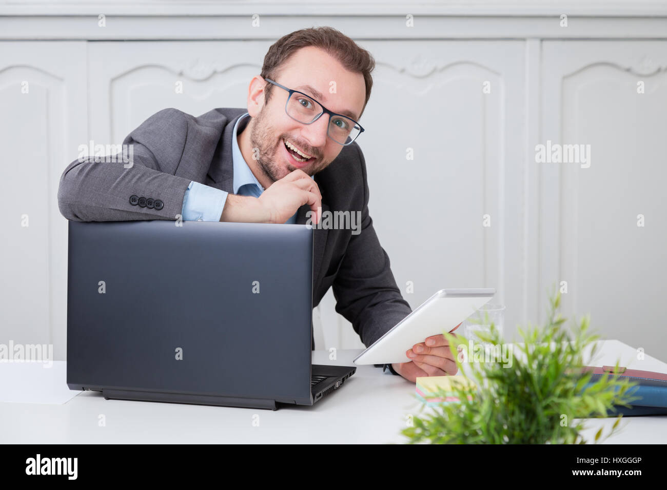Happy businessman at the office desk - Stock Image