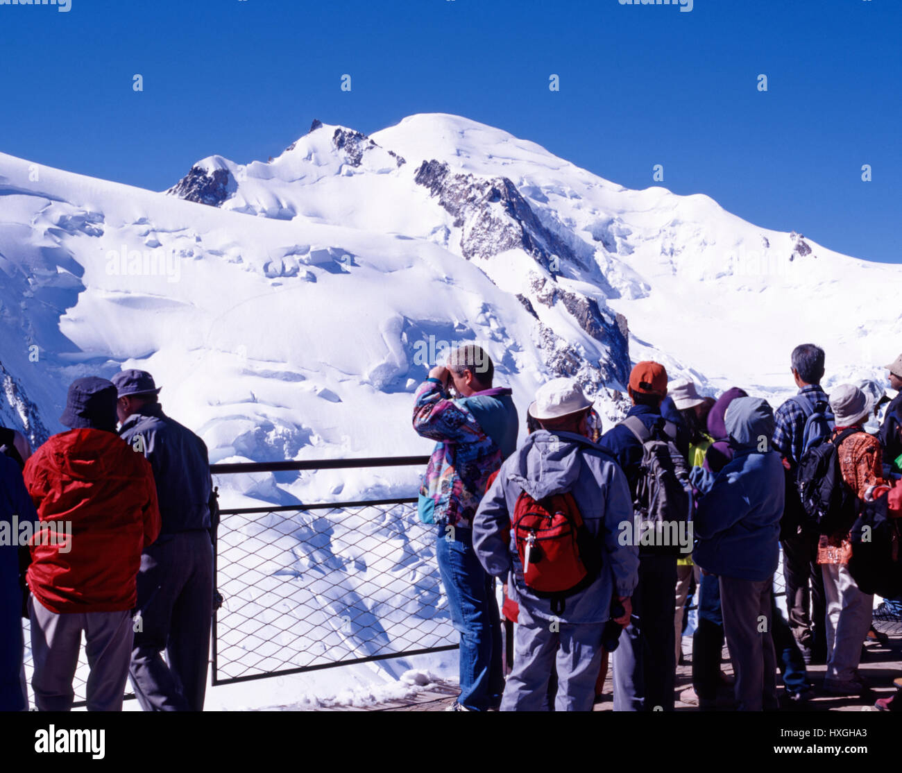 Tourists viewing Mont Blanc from Aguile de Midi, Chamonix, France - Stock Image