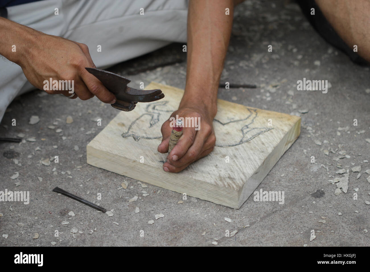 Hands of a man who is craving and working on a wooden plate.making an accessory  he could sell in market hand crafting - Stock Image