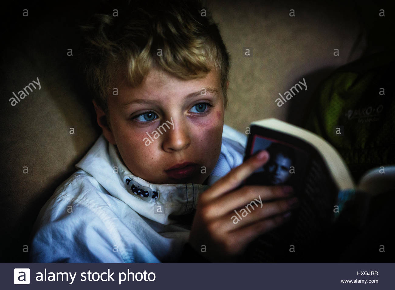 Young boy reading a book with a look of contemplation in his face - Stock Image