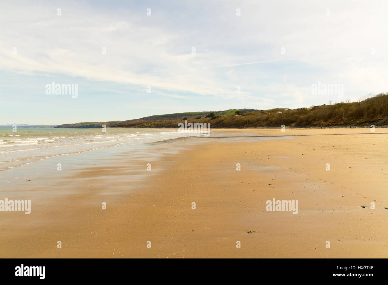 The sandy long empty beach in New Quay Wales - Stock Image