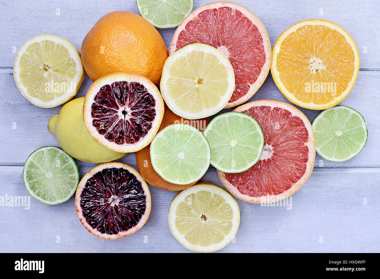 Variety of citrus fruits (orange, blood oranges, lemons, grapefruits, and limes) over a blue wood table top rustic - Stock Image