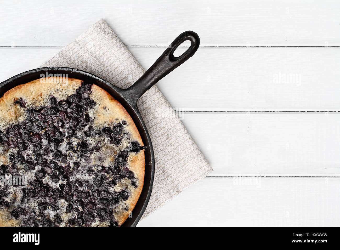 Above image of a blueberry cobbler baked in a cast iron skillet over a white wood table top. Image shot from overhead. - Stock Image