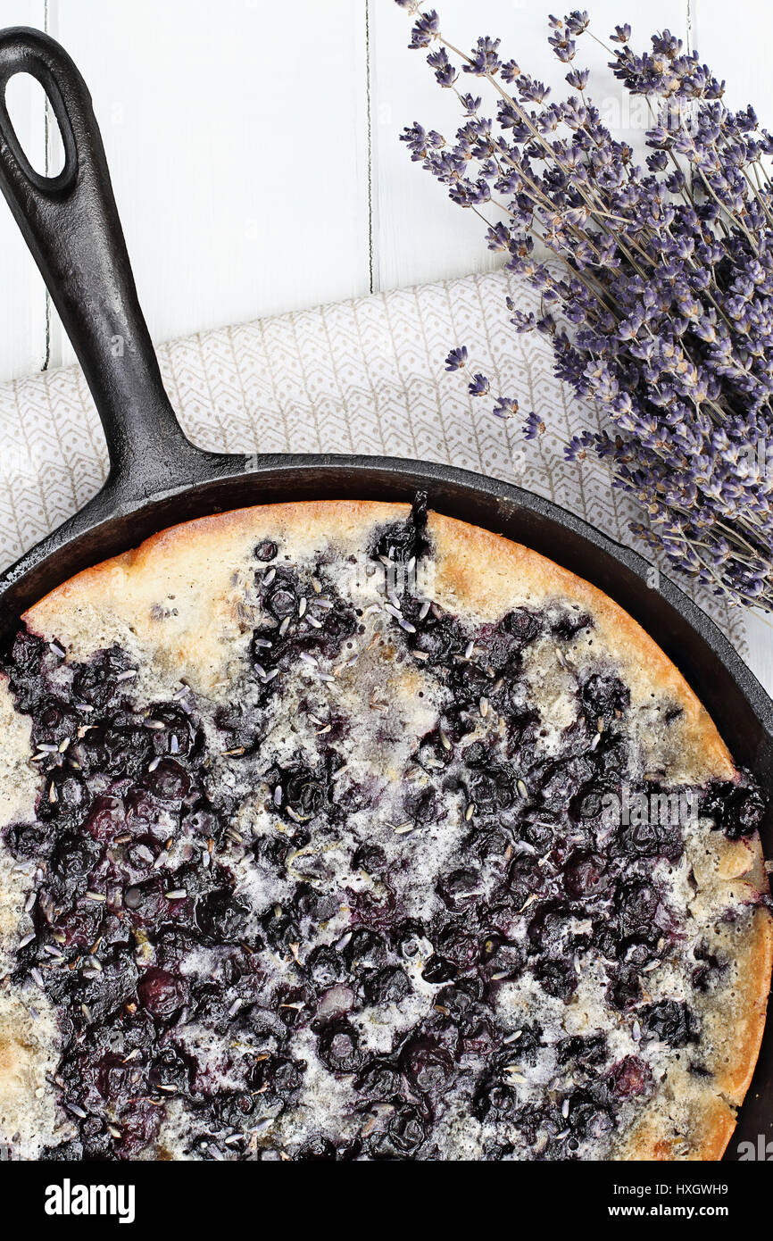 Above image of a blueberry lavender cobbler baked in a cast iron skillet over a white wood table top. Image shot - Stock Image