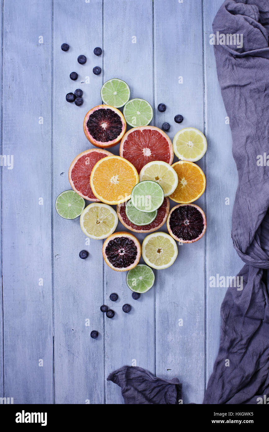 Variety of citrus fruits (orange, blood oranges, lemons, grapefruits, and limes) with blueberries with grey fabric - Stock Image
