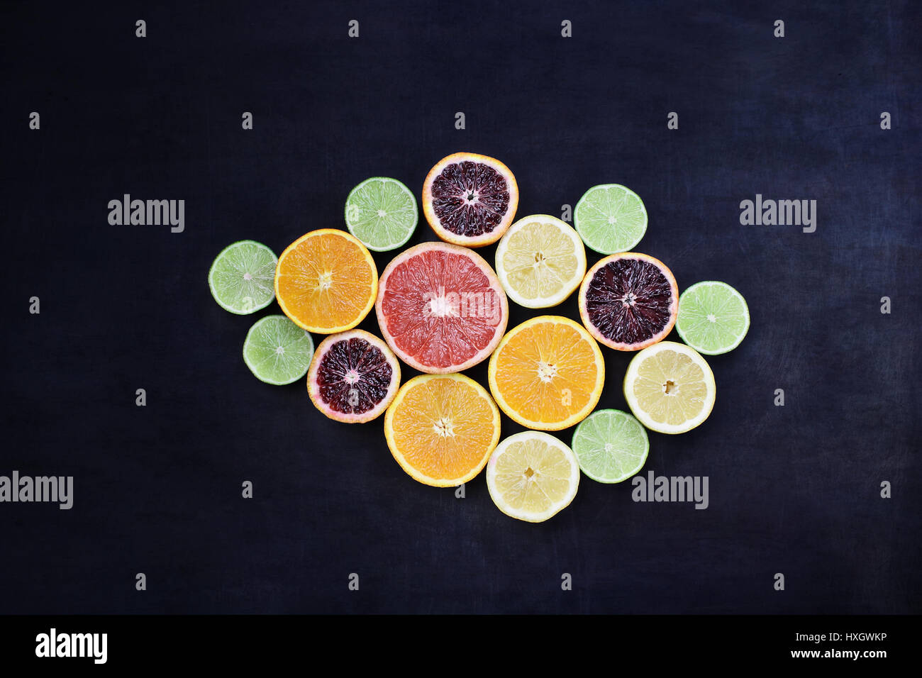 Variety of citrus fruits (orange, blood oranges, lemons, grapefruits, and limes) over a black rustic background. Stock Photo