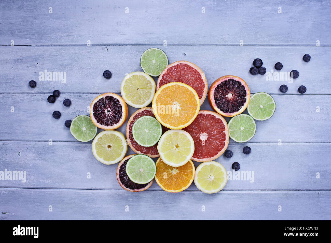Variety of citrus fruits (orange, blood oranges, lemons, grapefruits, and limes) with blueberries over a blue rustic - Stock Image