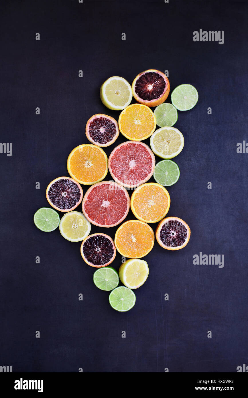 Variety of citrus fruits (orange, blood oranges, lemons, grapefruits, and limes) over a black rustic background. - Stock Image