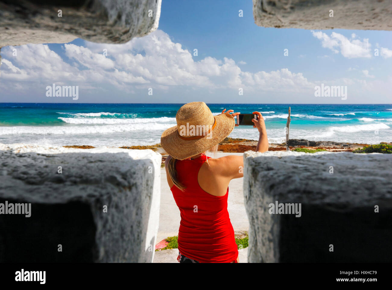 Looking trough the cross shape window to young woman how taking picture of Mexican coast - Stock Image