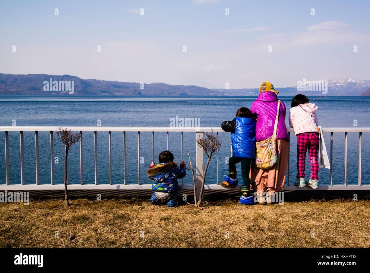 A family looking out the toya volcanic lake Hokaido Japan - Stock Image