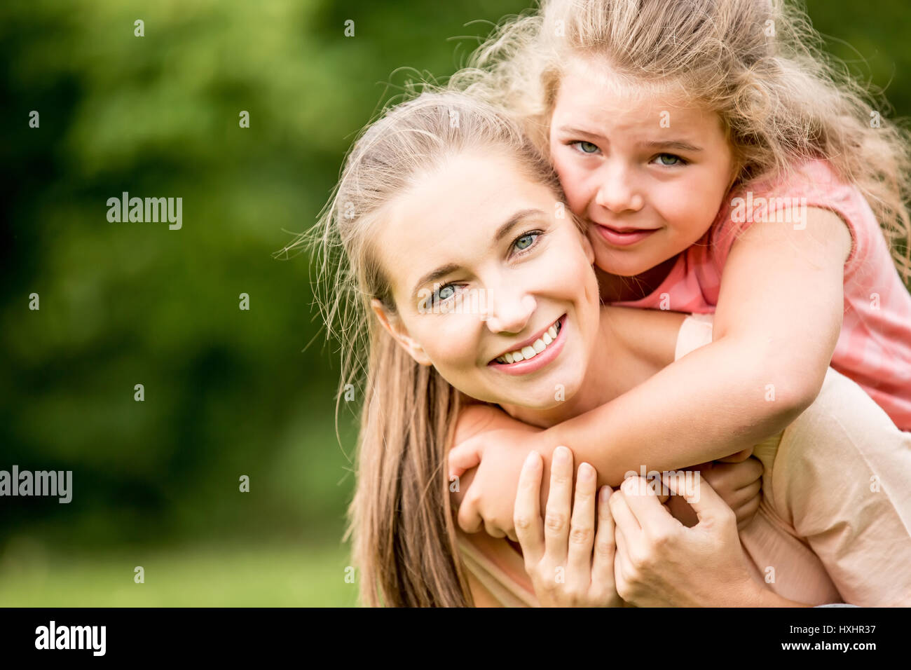 Mother and daughter happy together in summer in the nature - Stock Image