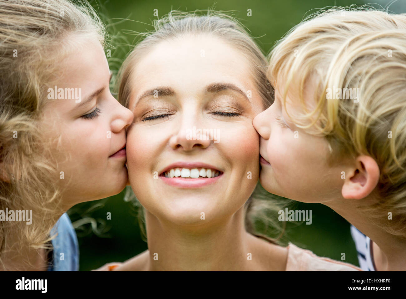 Children kissing mother with love as a happy family - Stock Image