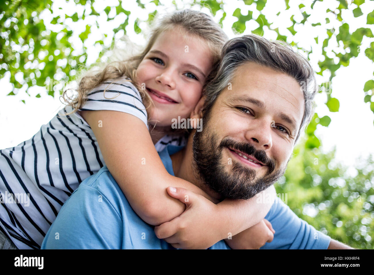 Daugther embrace father in piggyback ride at the park - Stock Image