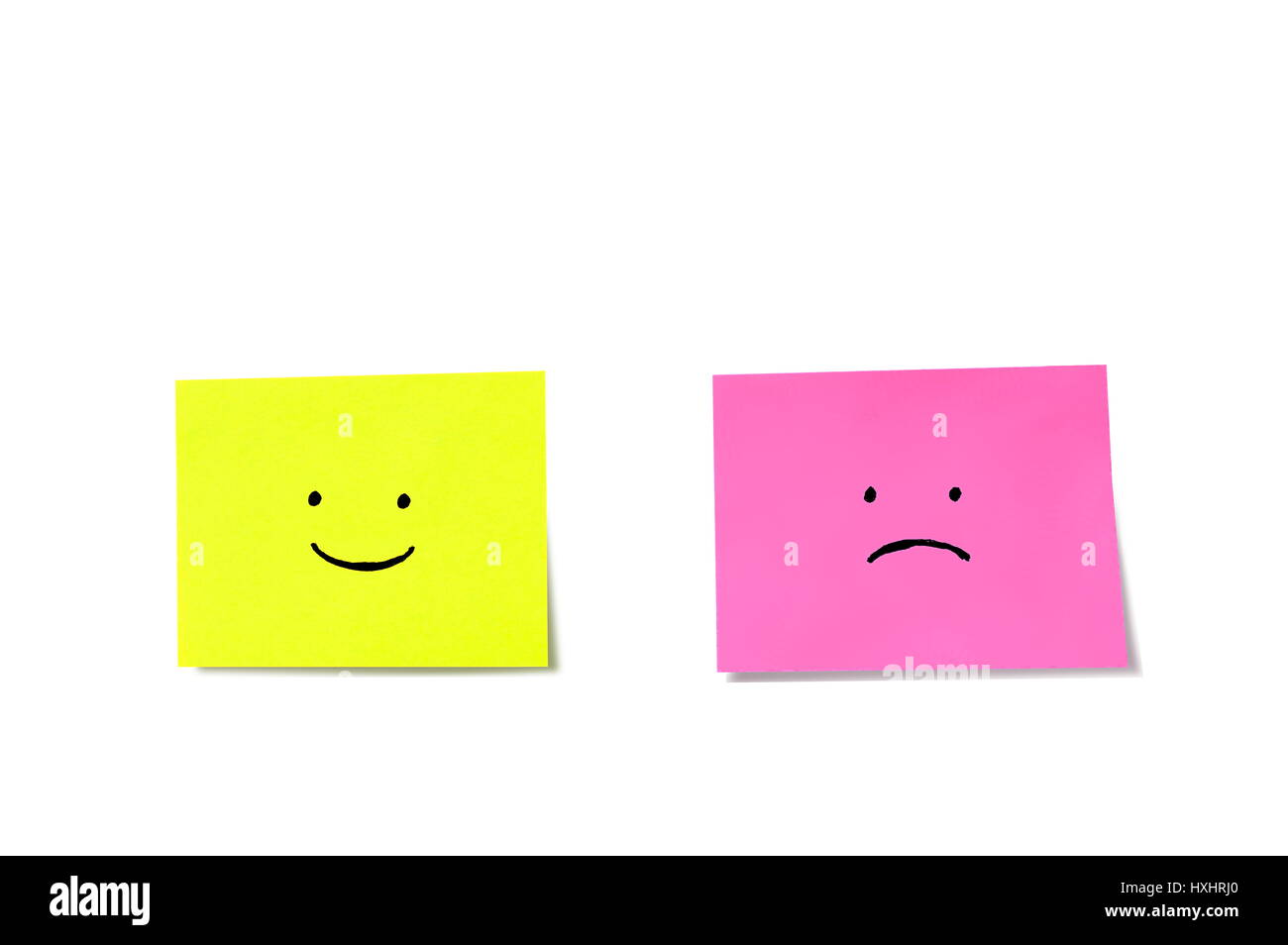 Happy and Sad face on sticky notes isolated on a white background - Stock Image